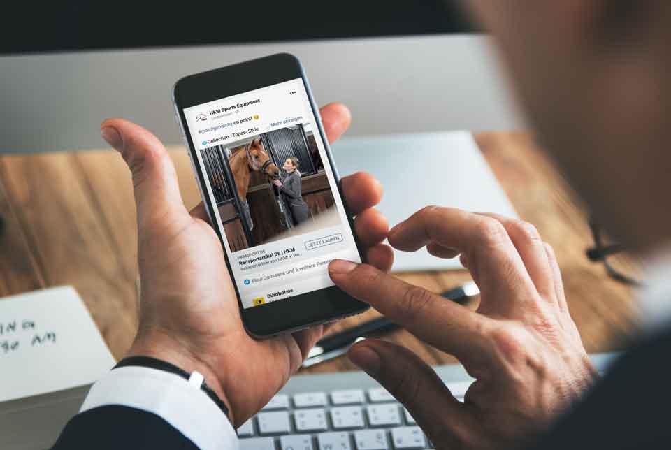 Person hält ein Mobilgerät in der Hand, auf welchem die Referenz dargestellt ist.