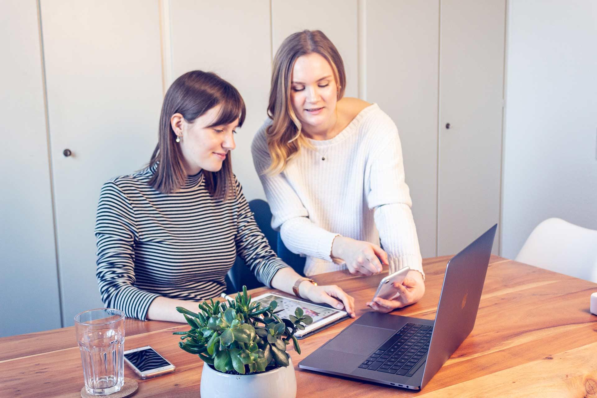 Zwei Mitarbeiterinnen schauen auf ein Mobilgerät.