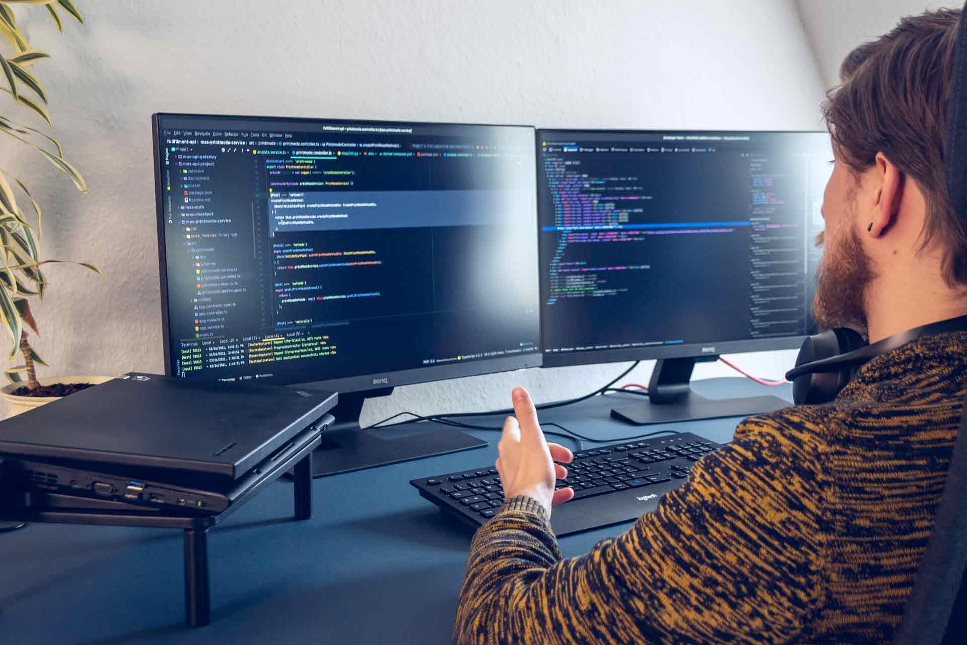 Mitarbeiter schaut auf seinen PC Bildschirm