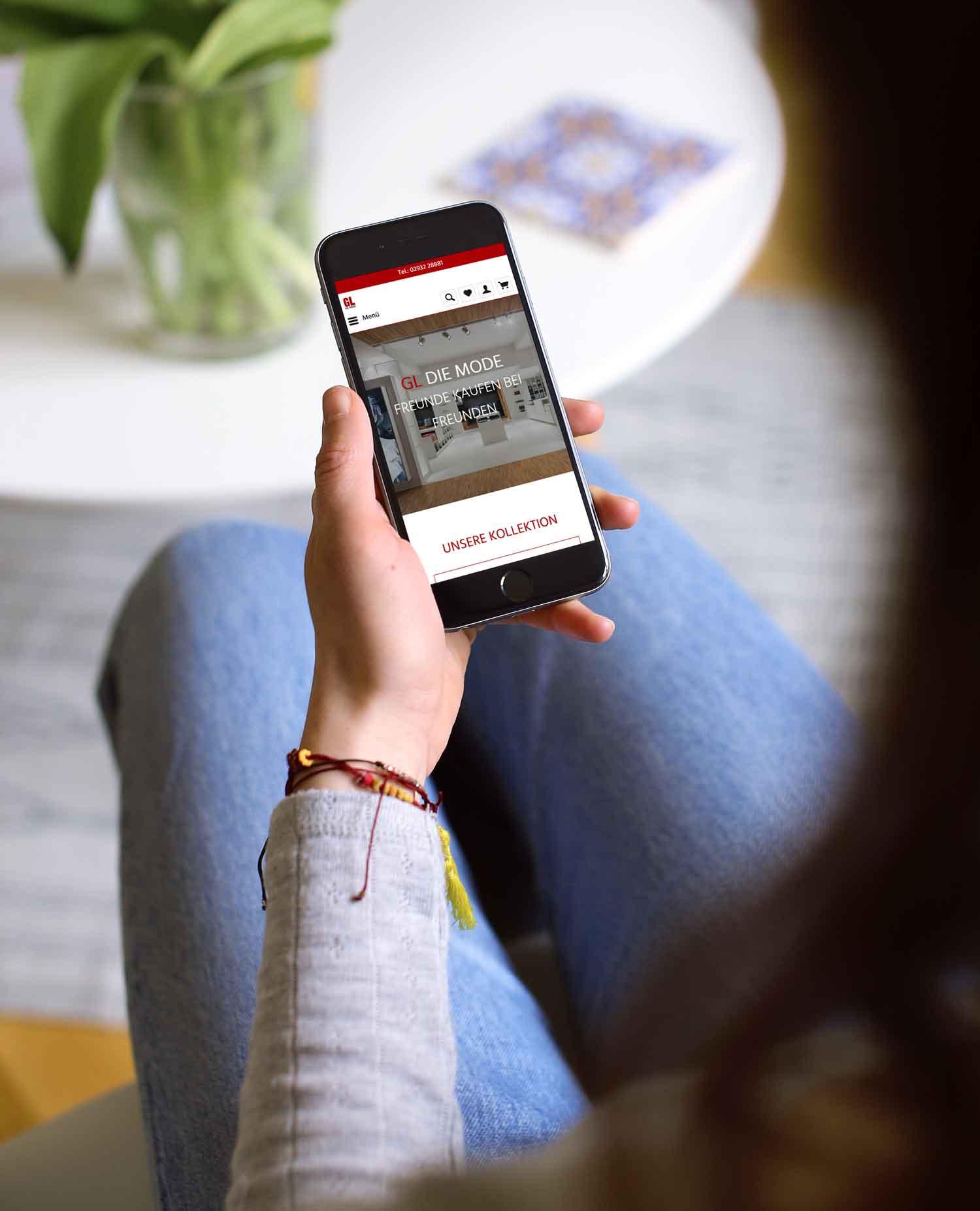 Person schaut auf ein Mobilgerät, auf welchem der Onlineshop von GL-Die Mode abgebildet ist.