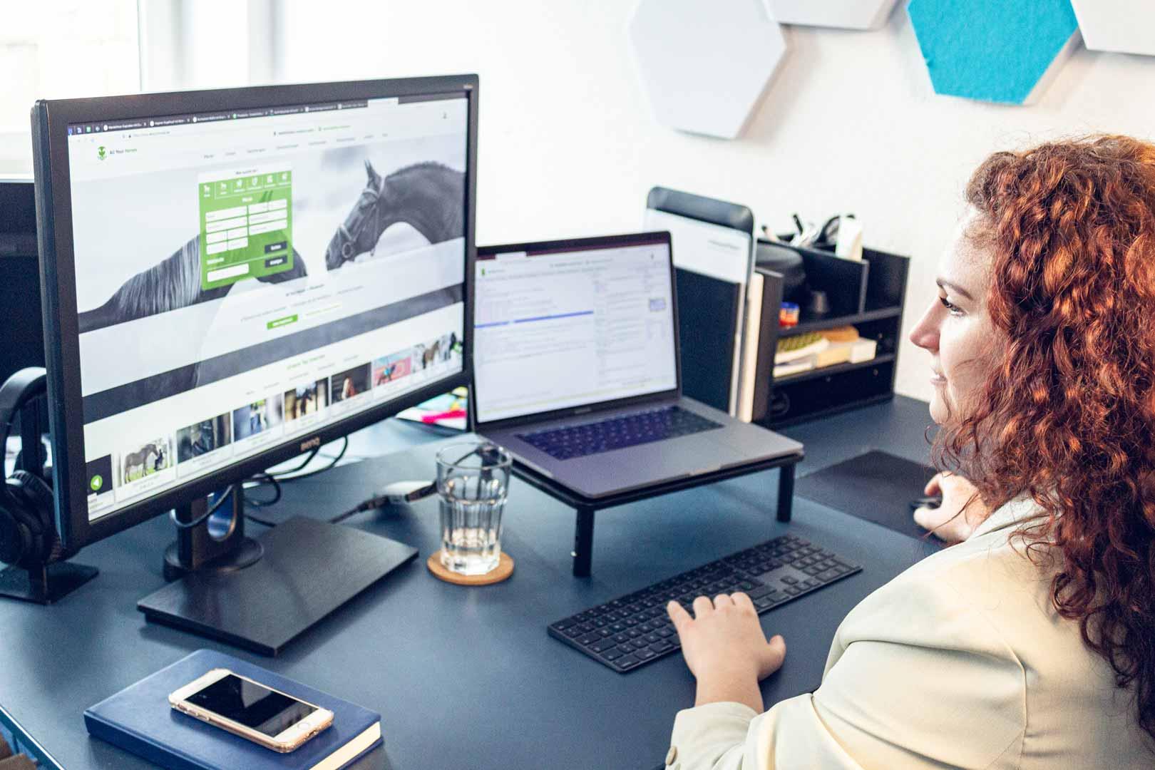 Mitarbeiterin schaut auf ihren Bildschirm, während sie arbeitet.