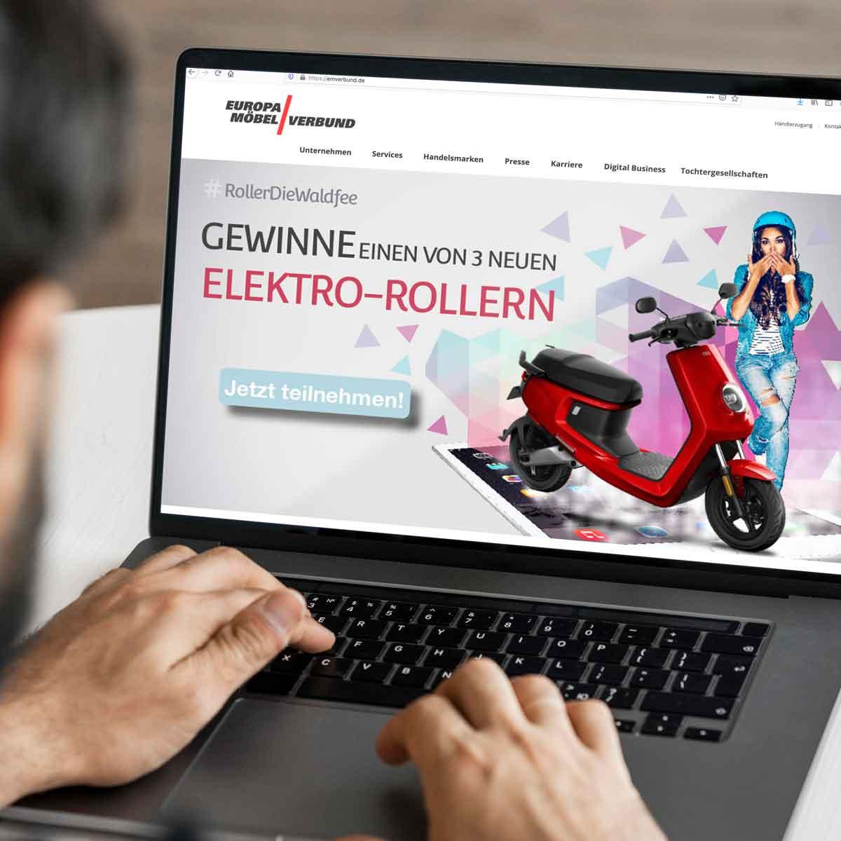 Mann sitzt vor einem Laptop, auf diesem sieht man eine Grafik zum Elektro-Roller-Gewinnspiel vom EMV