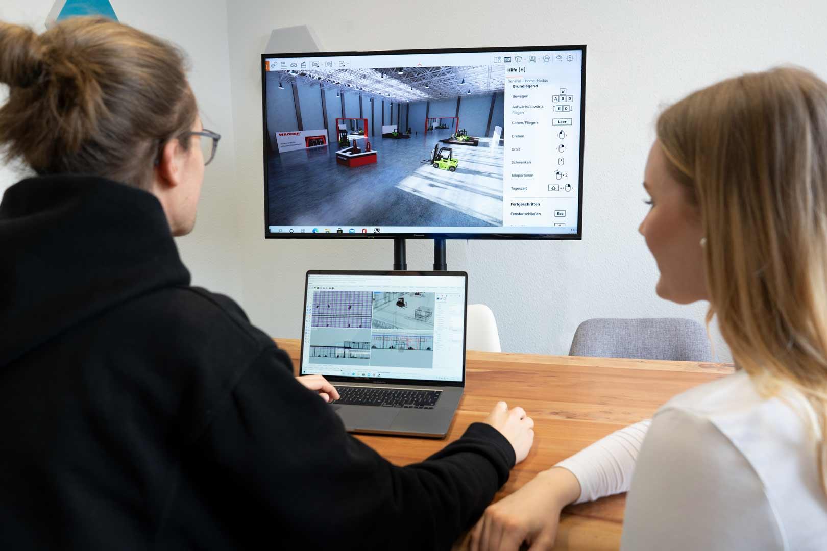 Zwei Mitarbeiter schauen auf einen PC-Bildschirm mit geöffnetem virtuellen Showroom
