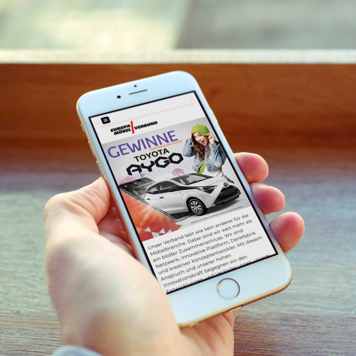 Handy in einer Hand zeigt einen Banner zum EMV-Autogewinnspiel