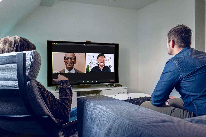 Zwei Mitarbeiter sitzen auf der Couch und führen ein Video-Gespräch.