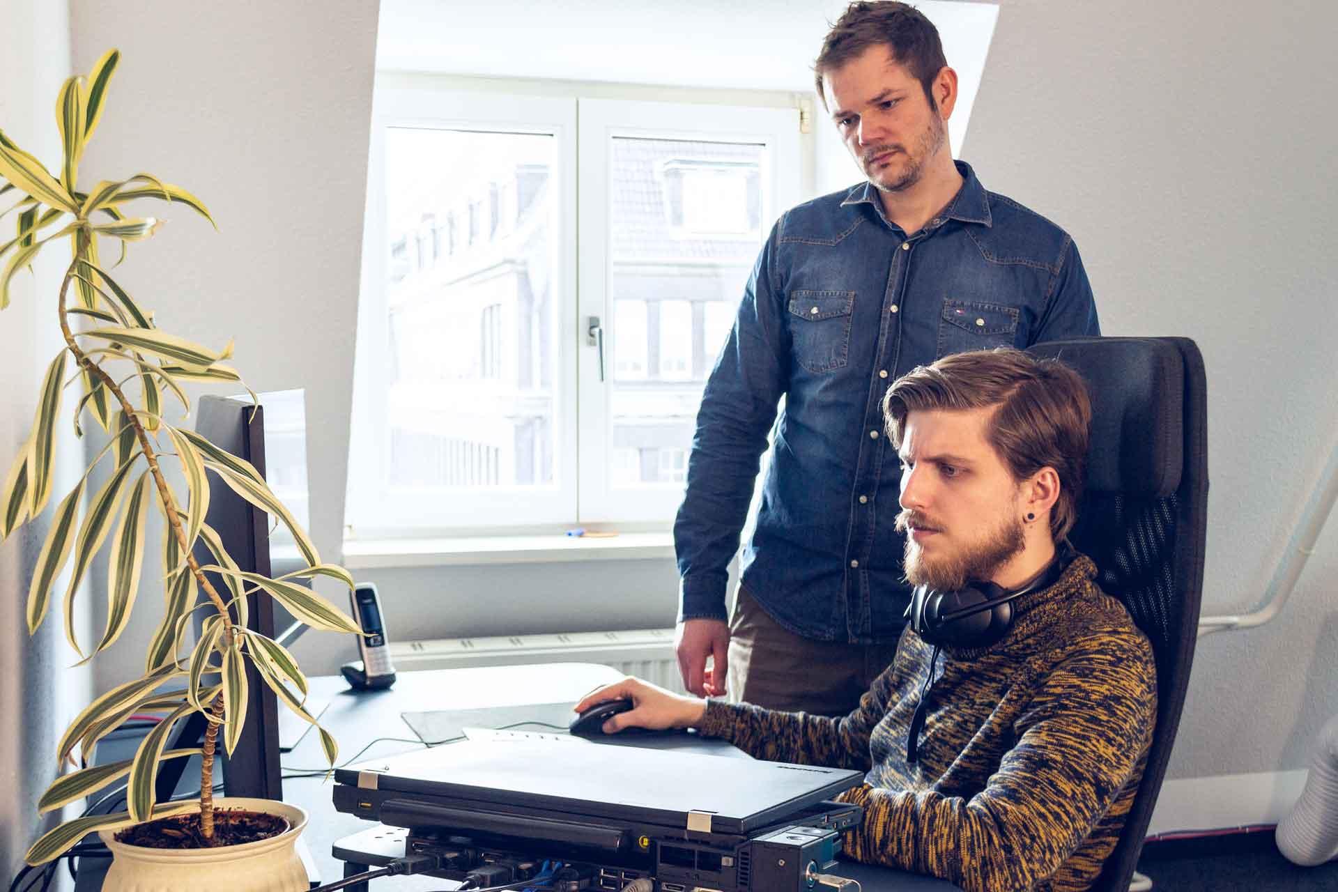 Zwei Mitarbeiter schauen gemeinsam auf einen PC-Bildschirm.