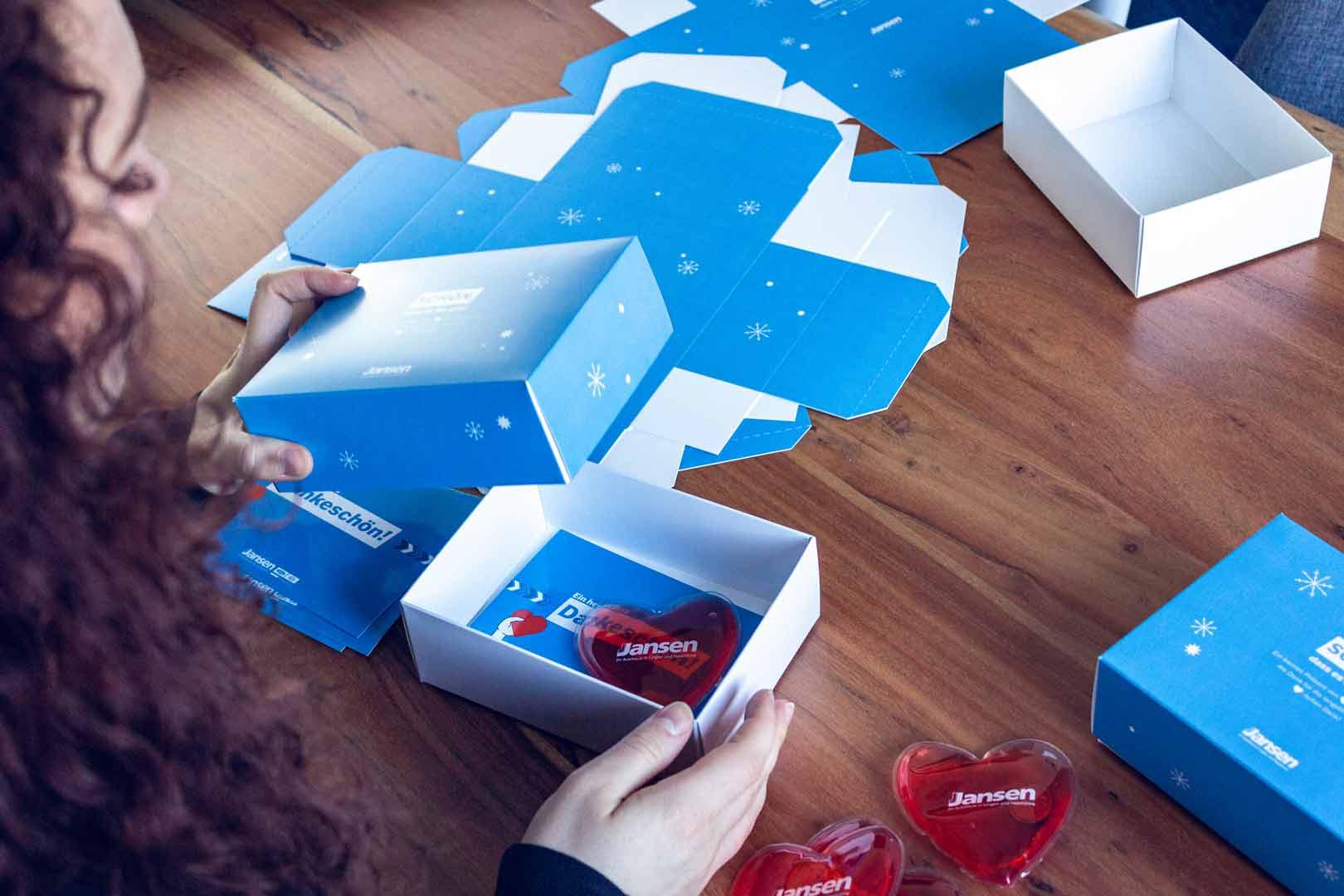 Person packt Geschenkboxen eines Kunden