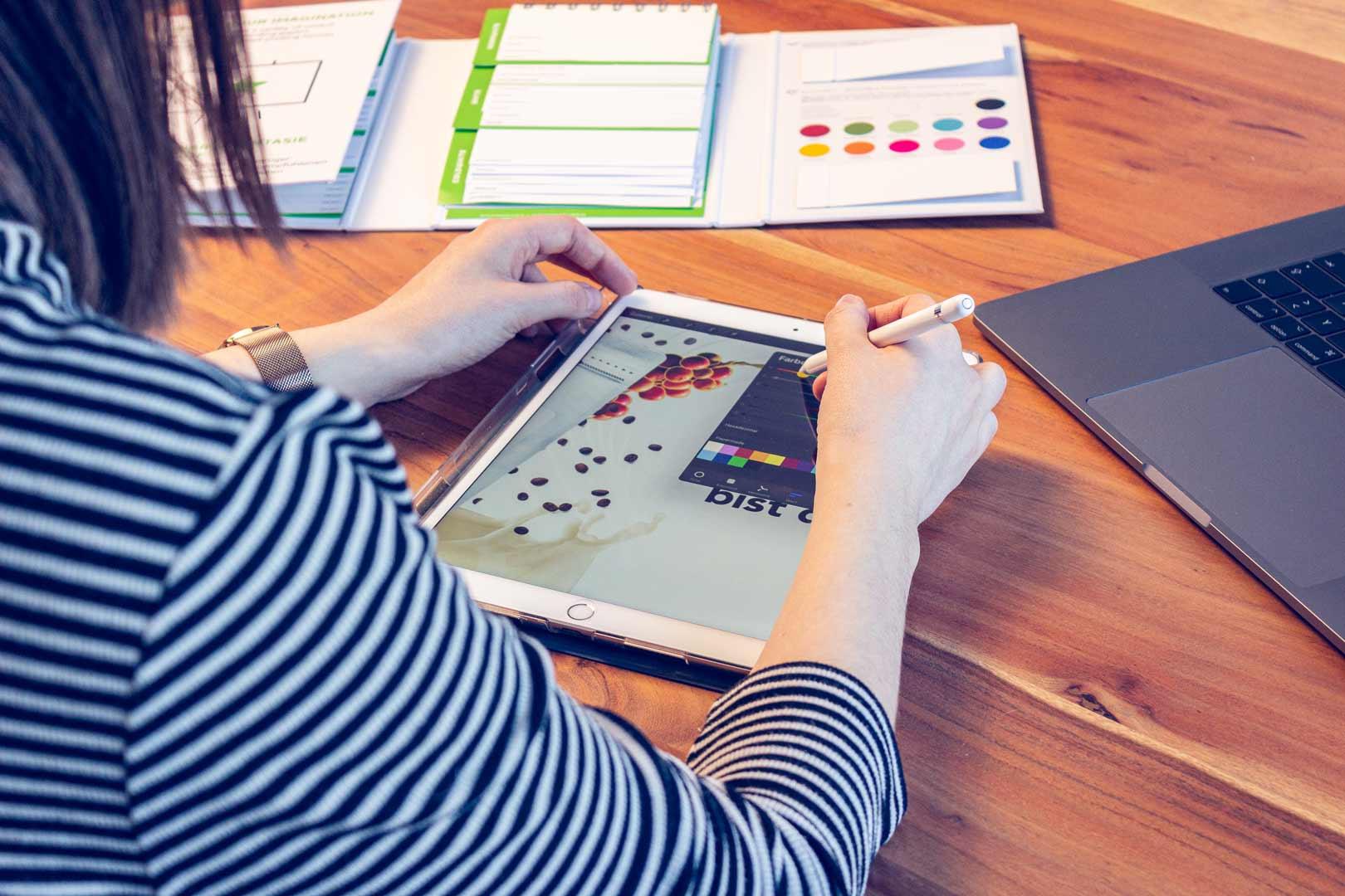 Mitarbeiterin schaut auf ein Tablet, mit dem sie arbeitet.