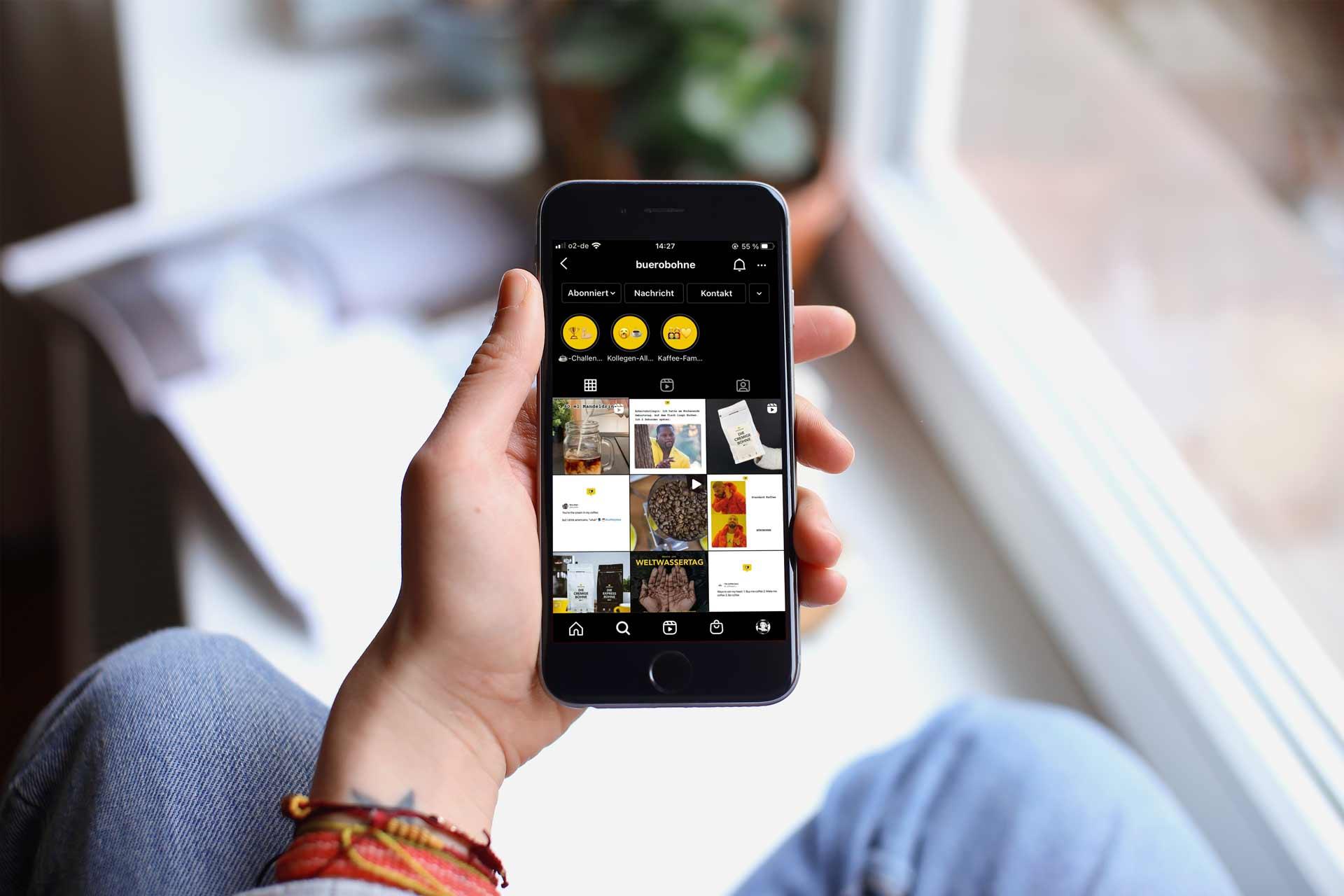 Perosn hält ein Mobilgerät in der Hand, auf welchem die Social Media Präsenz dargestellt ist.